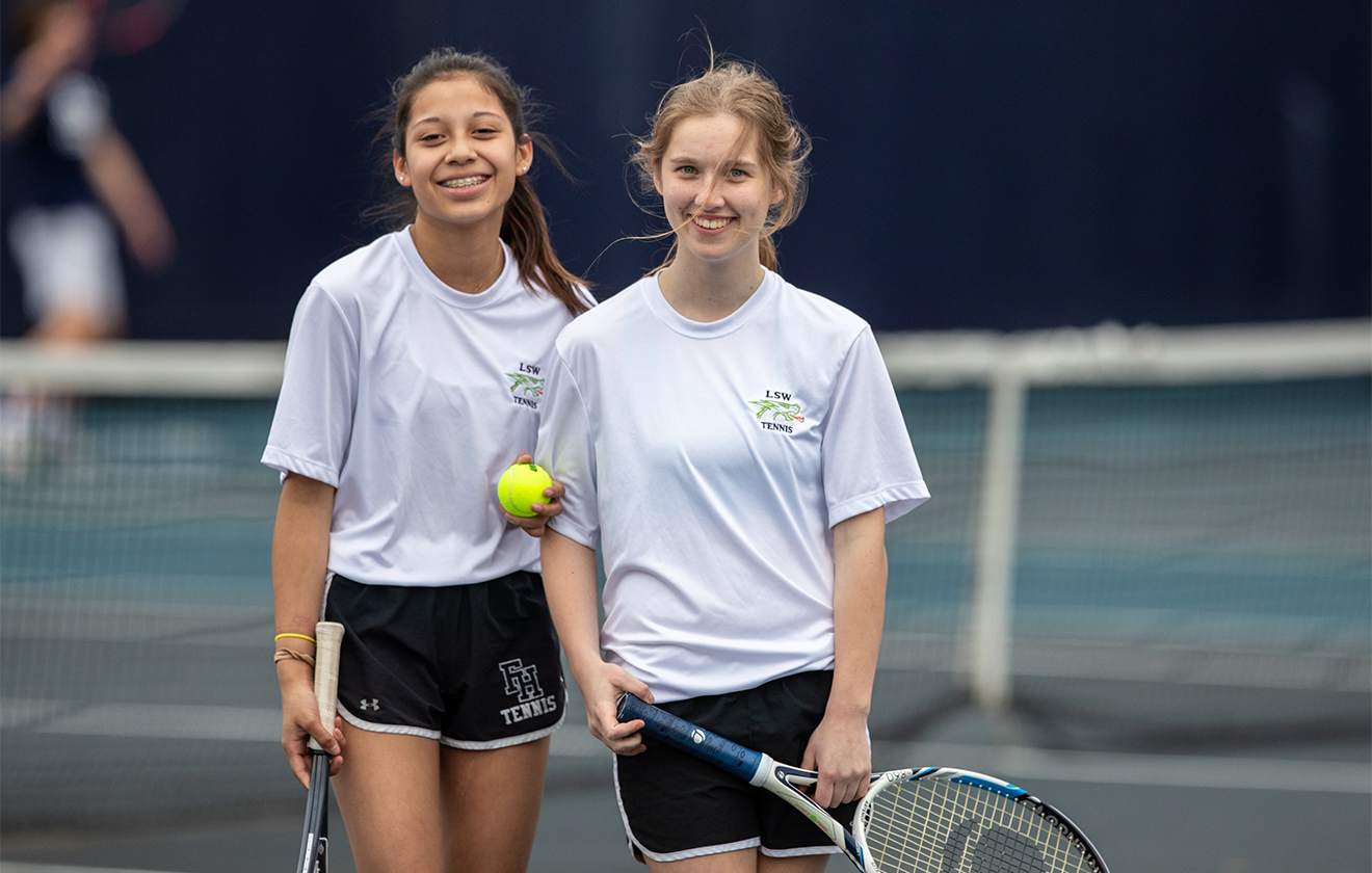Two girls smiling on tennis court