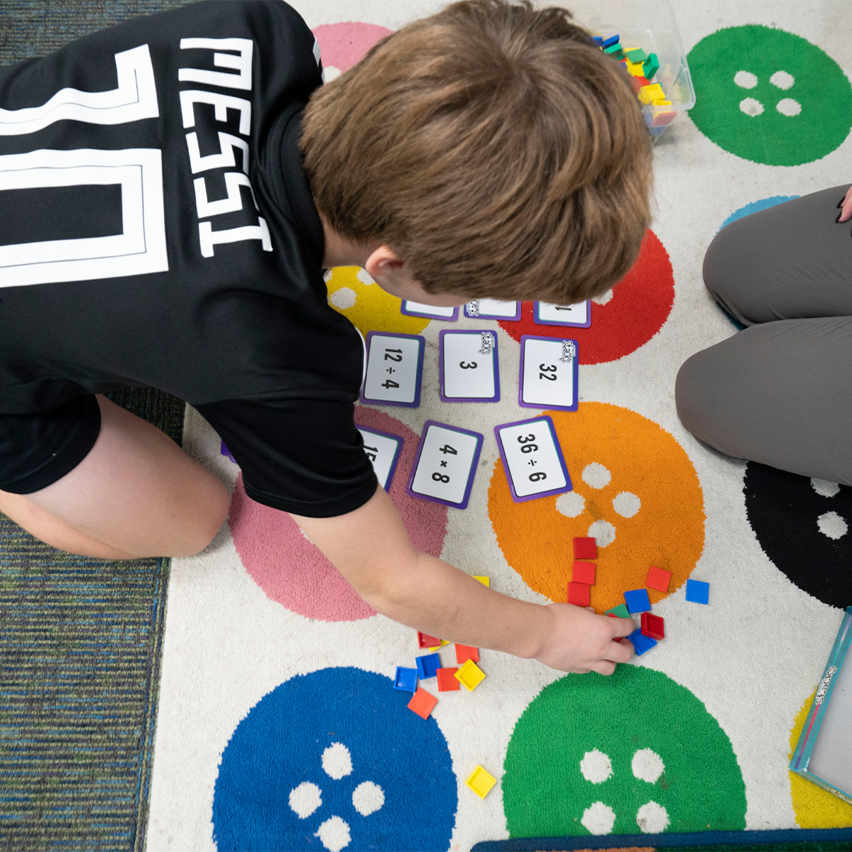 A student on the floor using math flashcards