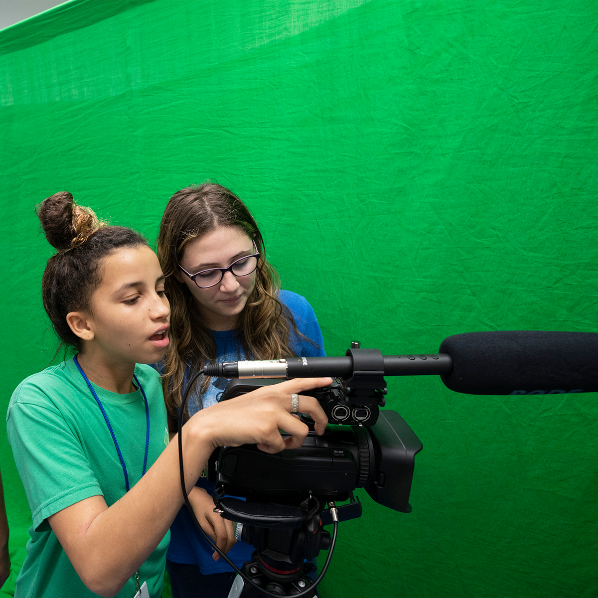 Two students using camera in front of a green screen