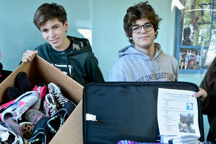 Four students hold suitcases full of donated clothes