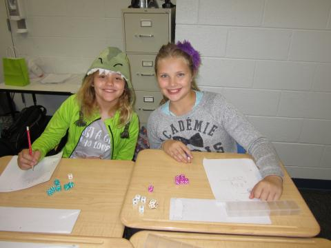 Two smiling students, one dressed in a dragon costume, work on an assignment at their desks