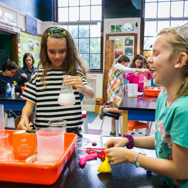 Two girls work on science experiment using beakers