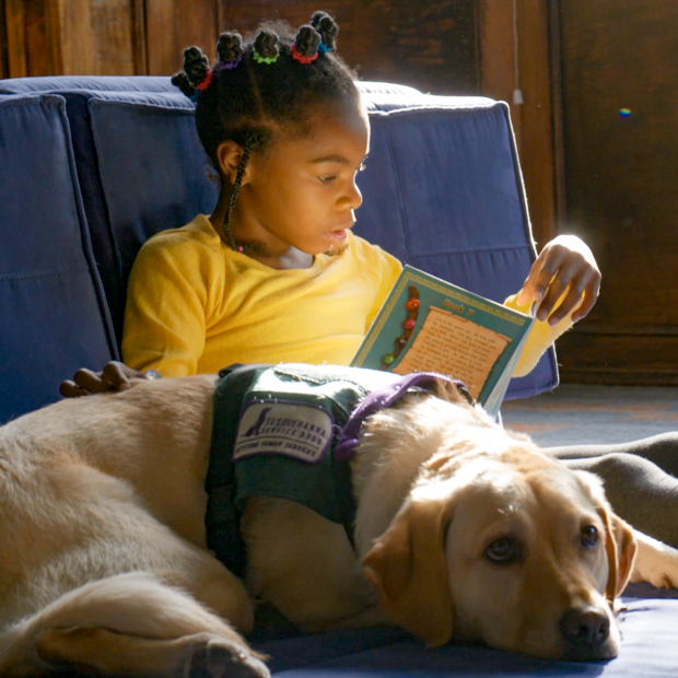Elementary student sitting on the floor with Bingo the dog reading a book