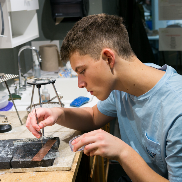 Student working with tweezers at metal smithing bench