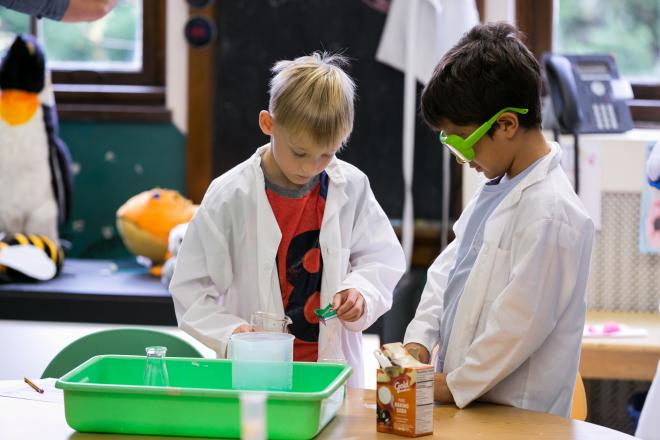 Two students wearing lab coats in science class