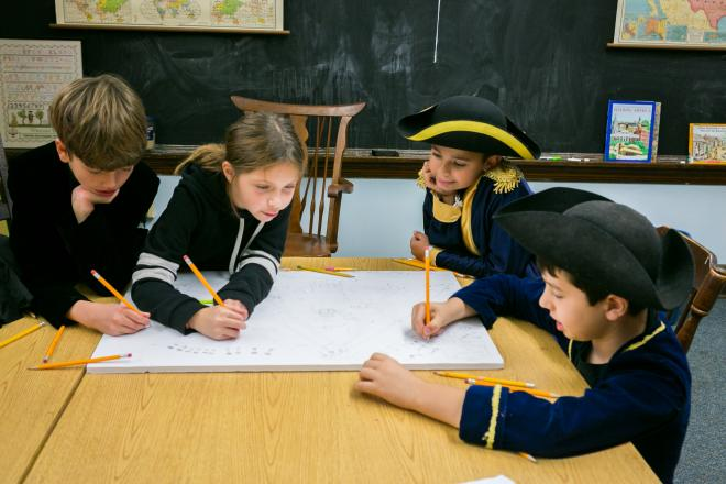 Students dressed in American Revolution gear work on project at table