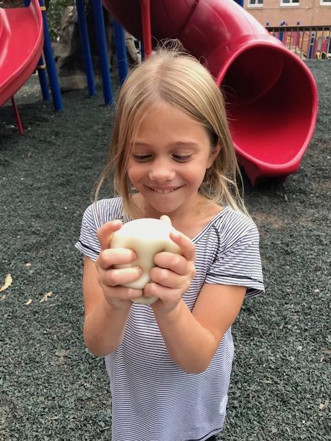 girl on playground squeezing something squishy