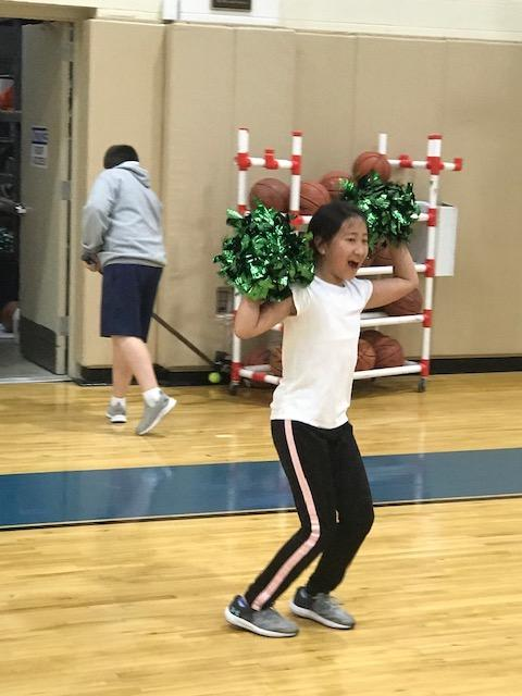 girl in gymnasium with pom-poms