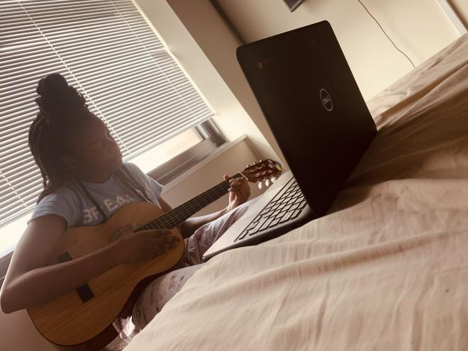 girl plays guitar on bed