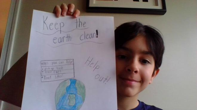 Student holds up drawing of the earth